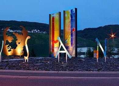 Kunstwerk an der Mosel: Der Cusanuskreisel in Bernkastel-Kues. Zu sehen ist die Kopfsilhouette des Theologen und Philosophen Nikolaus Cusanus sowie zwei farbige Glasstelen und die sieben Buchstaben des Namens Cusanus.